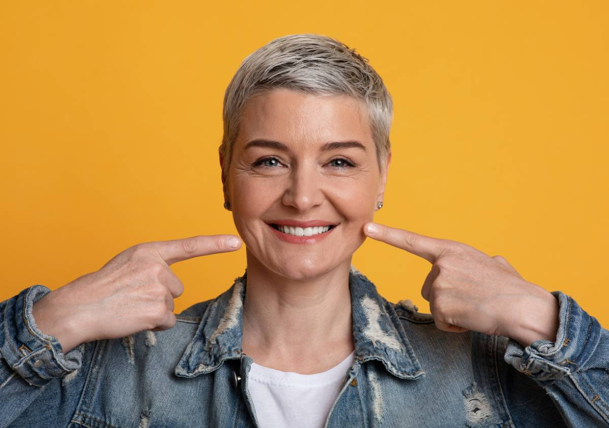 Woman with short hair and jean jacket smiling, pointing at smile with both hands