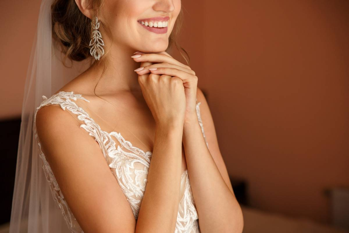 Young woman smiling with bright teeth on her wedding day in wedding gown.
